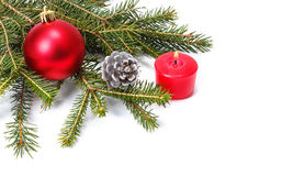 The branch of spruce, red ball, cones and red candle. On a white background Royalty Free Stock Photography