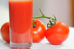 Branch of tomatoes behind glass of juice Stock Photos