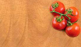 Branch tomatoes on wooden board Royalty Free Stock Photography