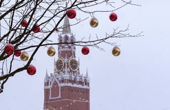A branch of the tree is decorated with Christmas decorations on the background of the Spasskaya Tower. Moscow. Kremlin royalty free stock images