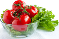The branch of whole red tomatoes. And lettuce. Isolated on white. Healthy vegetarian food Royalty Free Stock Photography