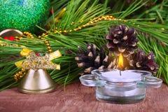 Branche décorative de sapin de bougie de Noël avec la cloche d'or et la prison Image libre de droits