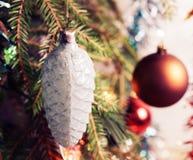 Branche d'arbre de Noël avec des boules de Noël sur le fond brouillé, et guirlandes de tresse cru images stock