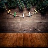 Branche d'arbre de Noël et pinces à linge sur la corde sur un mur en bois o Photographie stock libre de droits