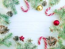Branche d'arbre de Noël, pinecone, sucrerie décorative de fête de neige sur une boule en bois blanche de carte de fond images stock