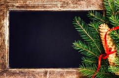 Branche d'arbre de sapin de Noël sur le tableau noir de vintage avec le cône et Photo stock