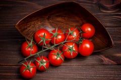 Branche de cerise de tomates dans une cuvette brune en bois Images libres de droits