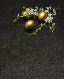 Branche de fleur de prune et oeufs de pâques sur le cou antique de granit de Brown Photos stock