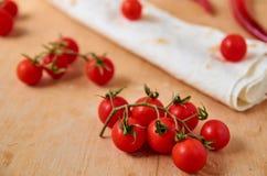 Branche des tomates-cerises rouges d'isolement sur le fond en bois brun clair Sur le poivre, les tomates et le pain pita de pimen Photographie stock