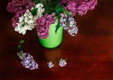 Branche deux du lilas blanc et pourpre dans le broc en plastique vert Tableau en bois, foyer sélectif Photos libres de droits