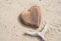 Branche en bois d'und de coeur sur le sable sur la plage Photo libre de droits