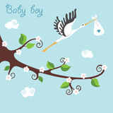 Branche fleurissante de bande dessinée mignonne Cigogne de vol avec le bébé garçon nouveau-né Photo libre de droits