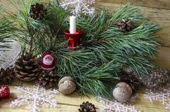 Branche pelucheuse de pin avec une bougie et une Santa Claus Photos stock