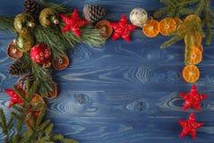 Branche verte et décorations rouges de Noël sur des conseils Images stock