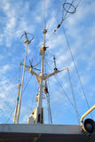 Branched antenna wire of the ship against blue sky Stock Photo