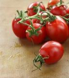 Branchement des tomates-cerises sur un vieux hachoir en pierre rustique Photo libre de droits