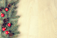 Branches of blue spruce, red balls and fir cones on a wooden bac Stock Photos