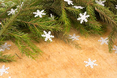 The branches of Christmas trees on the background of wooden boards and snowflakes. Royalty Free Stock Photography