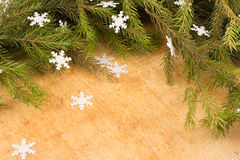 The branches of Christmas trees on the background of wooden boards and snowflakes. Stock Photo