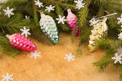 The branches of Christmas trees and  fallal cone decorations on the background of wooden boards and snowflakes. Stock Photo