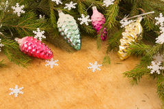The branches of Christmas trees and  fallal cone decorations on the background of wooden boards and snowflakes. Stock Photos