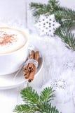 Branches d'arbre de cappuccino et de Noël de café d'hiver Tasse blanche de cappuccino avec de la cannelle sur un fond en bois image stock