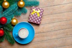 Branches d'arbre de sapin, tasse de café, cadeau et babioles colorées sur t Photos stock