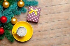 Branches d'arbre de sapin, tasse de café, cadeau et babioles colorées sur t Photos libres de droits