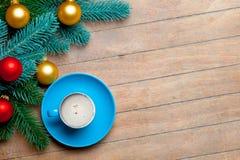 Branches d'arbre de sapin, tasse de café et babioles colorées sur gagné Image libre de droits