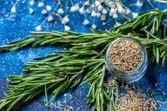 Branches du romarin frais, romarin sec dans un pot en verre sur un fond bleu-foncé photographie stock