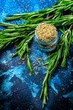 Branches du romarin frais, romarin sec dans un pot en verre sur un fond bleu-foncé images stock