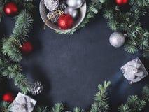 Branches et ornements verts de Noël sur le noir Photographie stock libre de droits