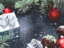 Branches et ornements verts de Noël sur le noir Images stock