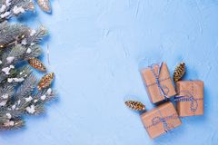 Branches fir tree and boxes with presents, fairy lights and golden pine cones on blue textured background. Top view royalty free stock image