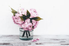 Branches of fruit tree in pink blossoms in vase on wooden table. Branches of fruit tree in pink blossoms with green leaves in transparent glass vase on vintage Royalty Free Stock Image