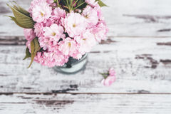 Branches of fruit tree in pink blossoms in vase on wooden table Stock Image