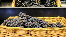 Branches of grapes in a wicker basket. Bundles of fresh ripe red grapes in the grocery store, selective focus. Grape stock images