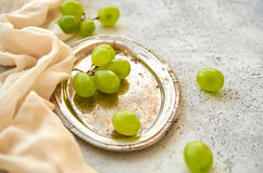 Branches of green grapes on silver vintage tray decorated with light brown cloth on gray concrete blurred background close up. Side view Royalty Free Stock Images