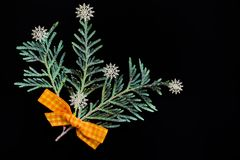 Branches of green juniper with a yellow bow made of fabric and white plastic snowflakes in the form of a bouquet Stock Images