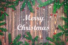 Branches impeccables avec les baies rouges sur une table en bois Joyeux Noël photos stock