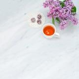 Branches lilas de fleur, tasse de thé et boules de bonheur sur Carrare mA Image stock