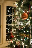 An old fashioned Christmas tree trimmed with pearls and an assortment of beautiful ornaments reflected in bay window royalty free stock photography