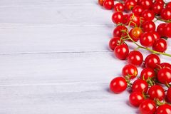 Branches of red organic fresh cherry tomatoes on a wooden background. stock photography