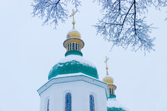 Branches under snow against the background of church Stock Photos
