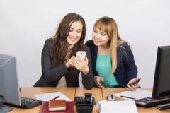 2 branchless работника восторженно смотря сотовый телефон на его столе Стоковое Изображение