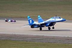 BRANCO de Mikoyan Gurevich MiG-29UB 1 da raça perfoming da força aérea do russo com o carro da fórmula 3 em Zhukovsky durante o a Imagens de Stock