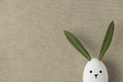 Branco decorativo o coelho pintado do ovo da páscoa com o Kawaii bonito tirado enfrenta O verde deixa as orelhas Fundo de linho b foto de stock