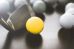 branco e bolas de golfe uma amarelas no assoalho preto individualidade imagens de stock royalty free