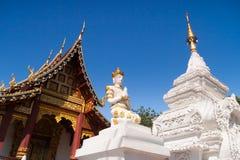 Branco e estátua de buddha do ouro na frente dos templos Foto de Stock