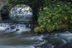 Branco leitoso girado da água de fluxo por uma exposição longa como flui em torno das rochas musgosos verdes e marrons imagem de stock royalty free